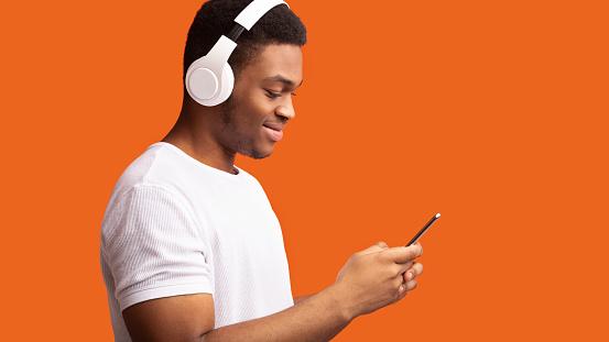 Enjoy Music. Smiling afro guy listening to podcast on cellphone using headphone set, orange studio background