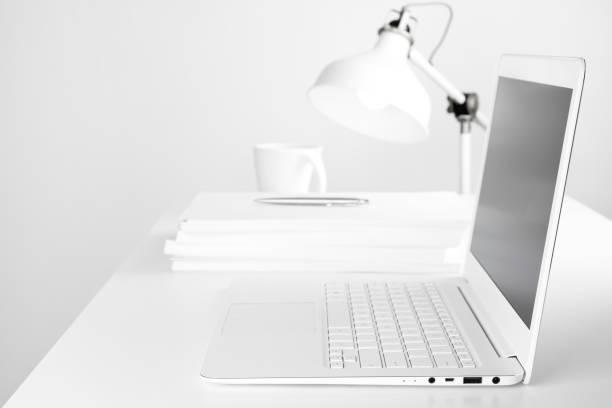 seitenansicht des verschwommenen arbeitsplatz innenraum mit laptop im fokus - schmaler tisch stock-fotos und bilder
