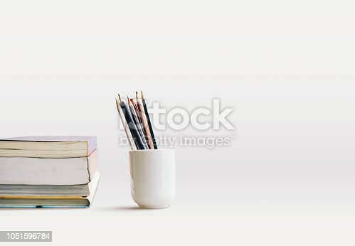 istock Side view of books stacking and cup of pencils, pens on the desk with copy space. Reading concept 1051596784