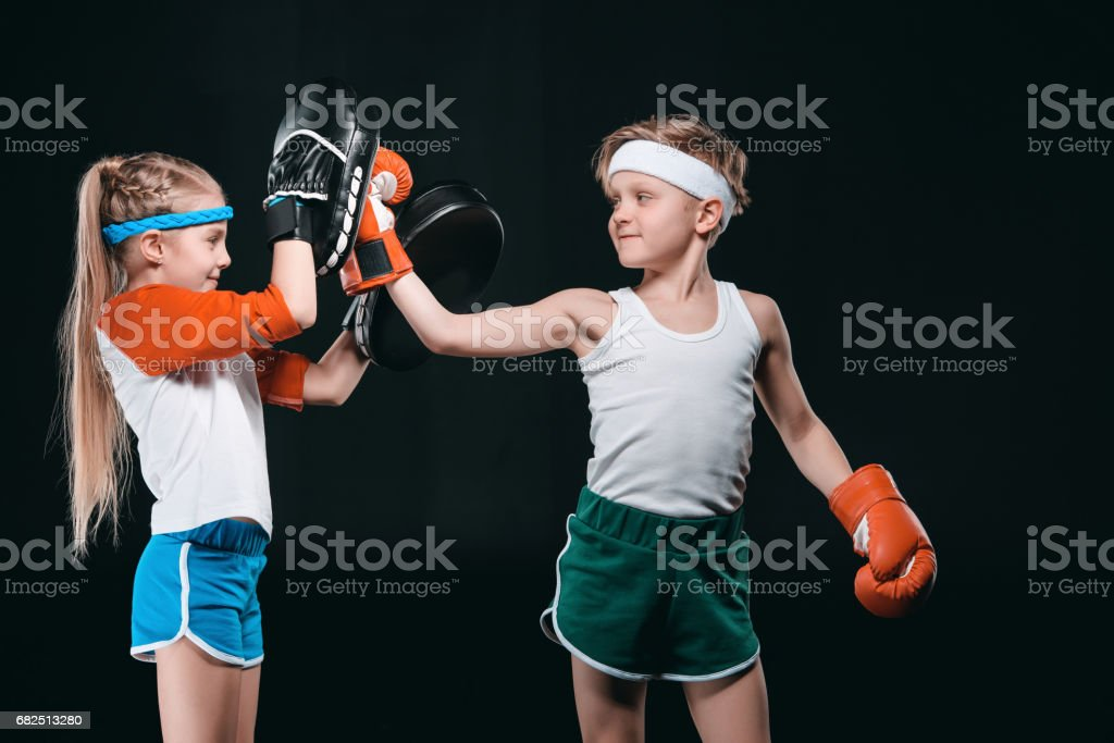 Side view of boy and girl in sportswear boxing isolated on black, activities for children concept Стоковые фото Стоковая фотография