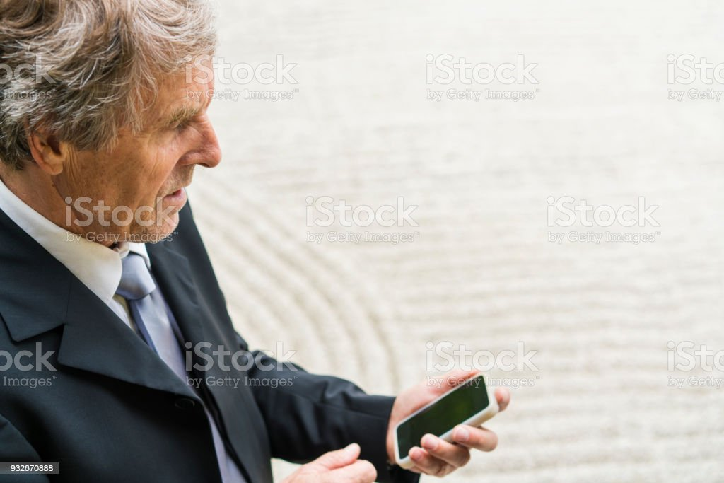 Side view of business man looking at mobile phone while enjoying Zen...