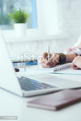 Side view of business woman making notes with silver pen in office background.