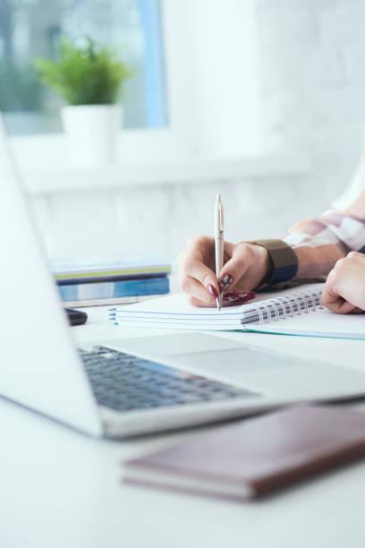 Seitenansicht der Geschäftsfrau, die Notizen mit silbernem Stift im Bürohintergrund macht. Spardarlehen und Kreditkonzeption für die Geschäftsfinanzierung. – Foto