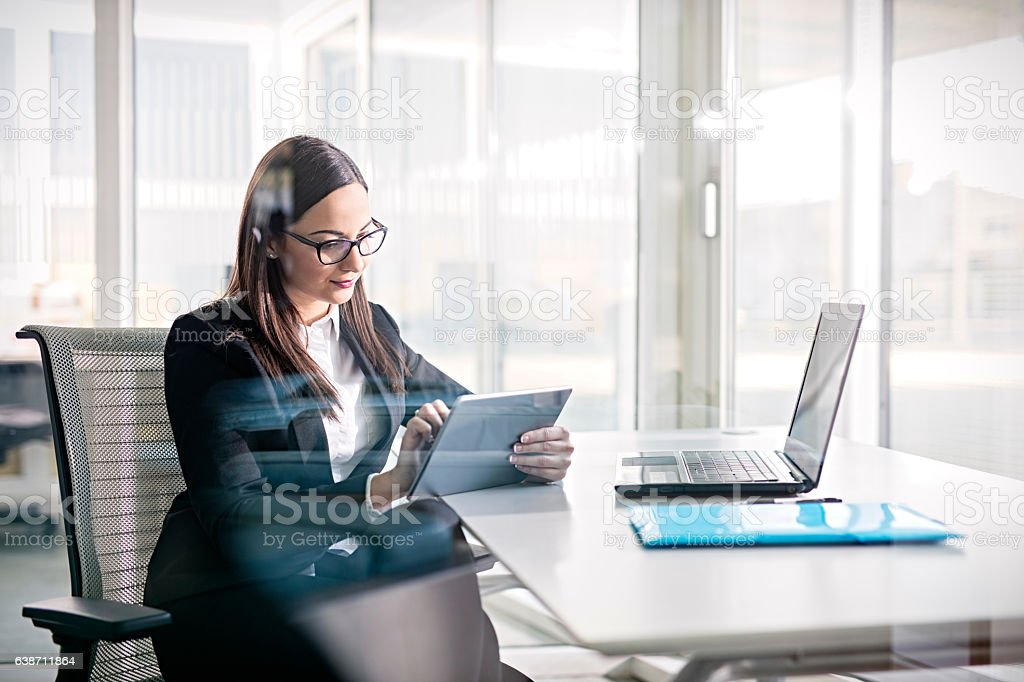 Side view of business woman working on digital tablet стоковое фото