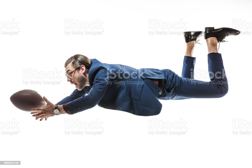 Side View Of Businessman Catching Rugby Ball While Falling