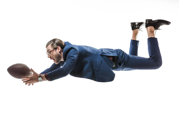 side view of businessman catching rugby ball while falling isolated on white side view of businessman catching rugby ball while falling isolated on white catching stock pictures, royalty-free photos & images