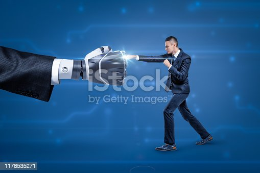 1050855372 istock photo Side view of businessman fighting big robot hand, bright white spark appearing at place where they touch. 1178535271