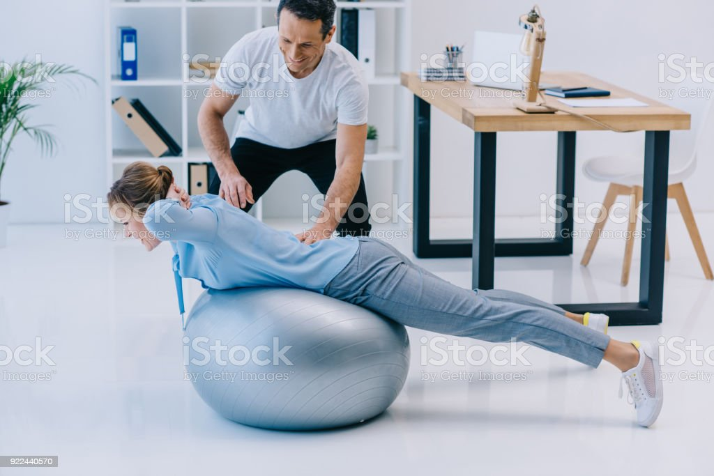 side view of businesswoman doing hyperextension exercise on fit ball with trainer at office stock photo