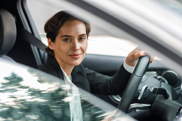 Side view of businesswoman driving car looking out of window. Portrait of a woman going to office in her car. stock photo