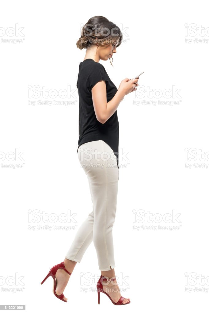 Side view of busy business woman in formal suit walking and typing on mobile phone. stock photo