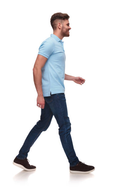 side view of casual man in blue polo shirt walking side view of casual man in blue polo shirt walking on white background and smiling, full body picture side view stock pictures, royalty-free photos & images
