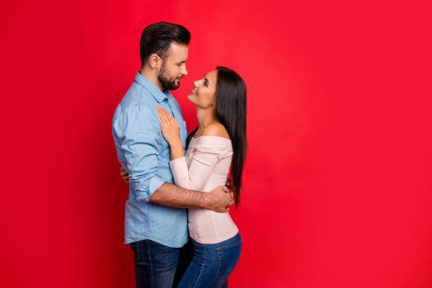 Side view of caucasian, attractive, smiling couple - bearded man embrace his charming, cute, pretty woman, looking to each other while standing over red background, 14 february stock photo