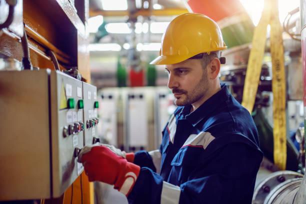 widok z boku pracownika kaukaskiego zakładu energetycznego w odzieży roboczej i z hełmem na głowie włączanie przełącznika. - elektryczność zdjęcia i obrazy z banku zdjęć