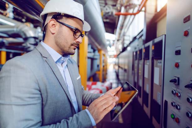발전소의 대시 보드 앞에 서있는 동안 태블릿을 사용하여 머리에 헬멧과 정장에 백인 감독자의 측면보기. - 석유 화학 공장 뉴스 사진 이미지