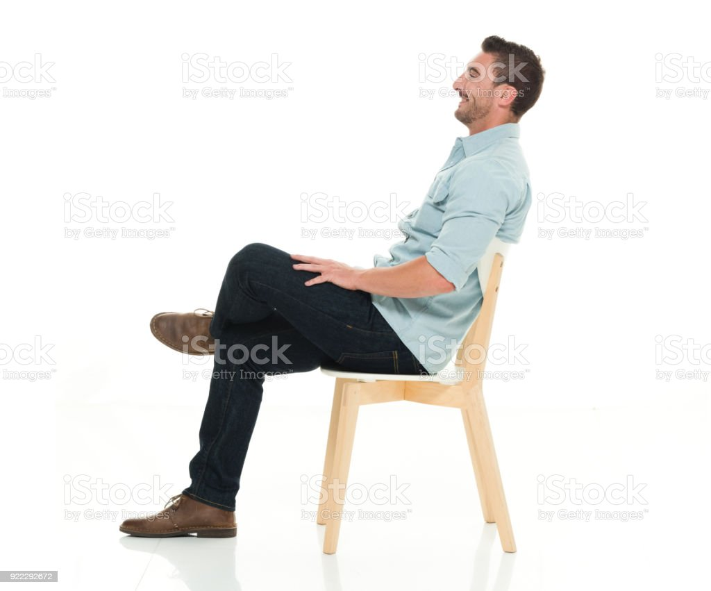 Side view of charming man seated stock photo