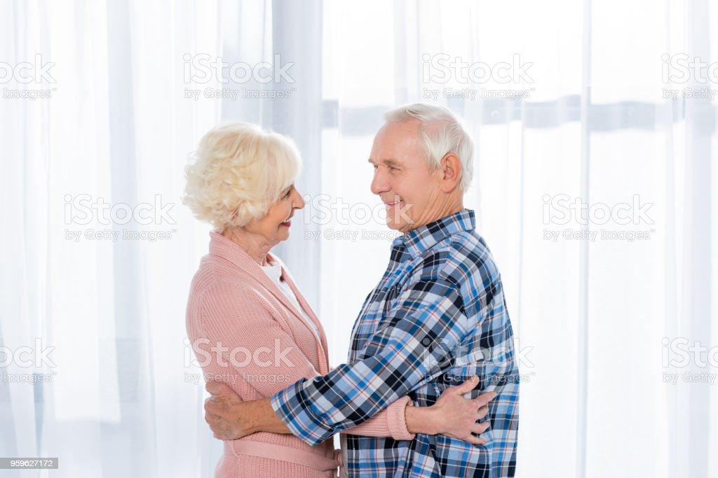 vista lateral de la alegre pareja senior abrazando y mirando el uno al otro - Foto de stock de Adulto libre de derechos