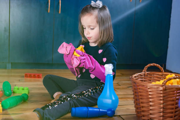Side view of child cleaning her toys at home Little girl sanitizing her toys wearing gloves kids cleaning up toys stock pictures, royalty-free photos & images