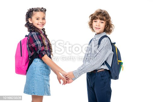 1016623732istockphoto side view of classmates holding hands and looking at camera isolated on white 1016623328