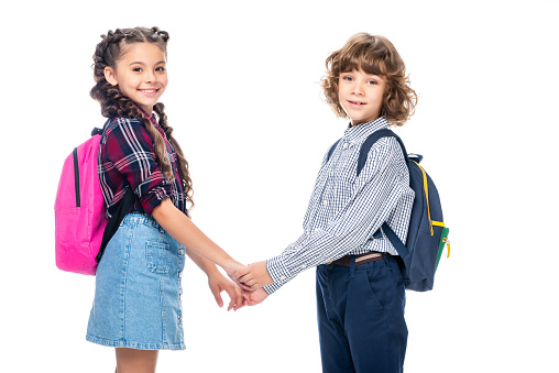 1016623732 istock photo side view of classmates holding hands and looking at camera isolated on white 1016623328