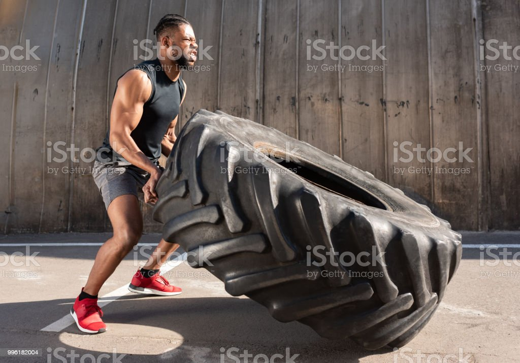 side view of concentrated african american sportsman training with tire on street stock photo