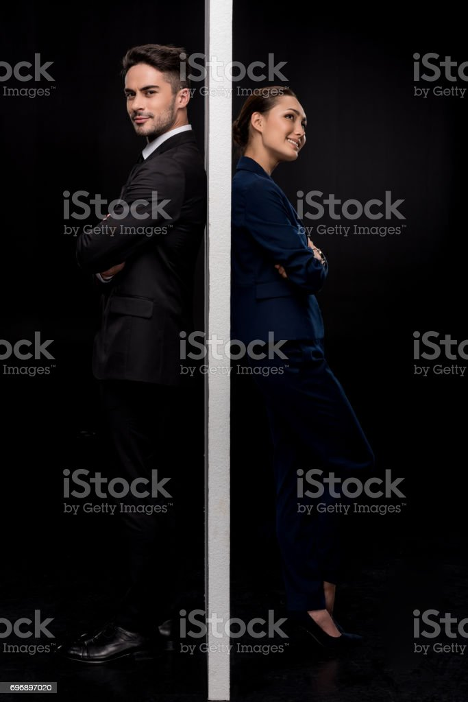 Side view of confident couple standing back to back near of separated wall stock photo