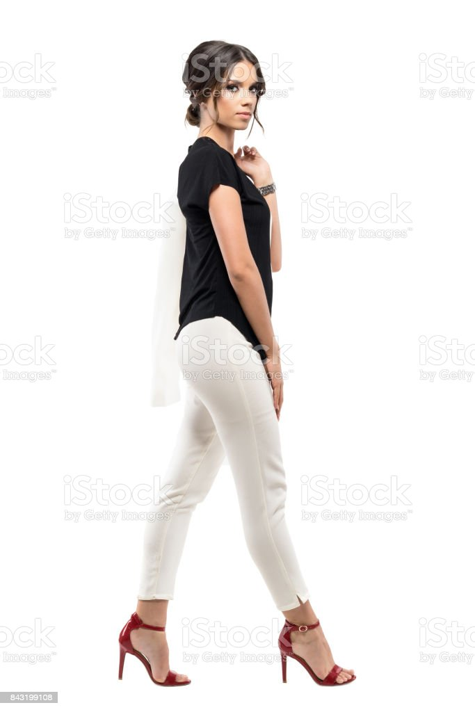 Side view of confident gorgeous business woman in suit walking and looking at camera stock photo
