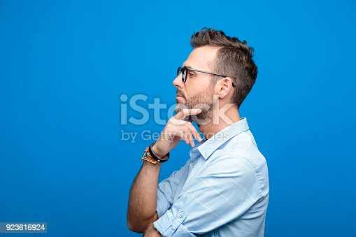 Summer portrait of confident, handsome man wearing blue shirt and glasses, looking away with hand on chin. Side view. Studio shot, blue background.