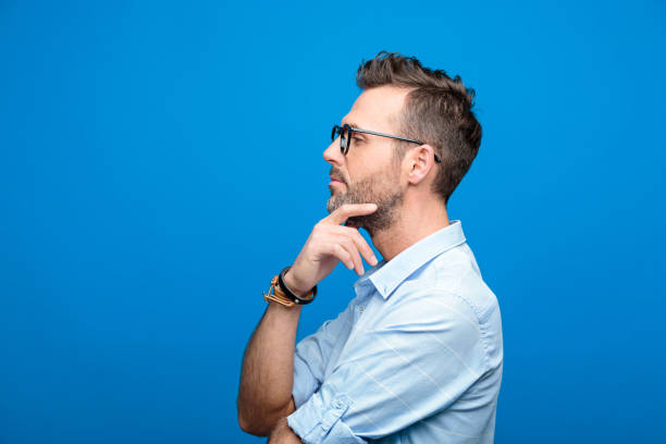 side view of confident, handsome man, blue background - ritratto uomo foto e immagini stock