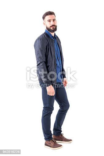 931173966istockphoto Side view of confident relaxed macho guy in bomber jacket posing and looking at camera 942516226