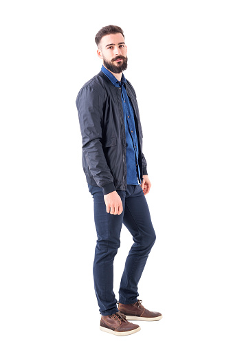 931173966 istock photo Side view of confident relaxed macho guy in bomber jacket posing and looking at camera 942516226