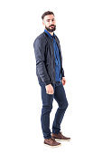 istock Side view of confident relaxed macho guy in bomber jacket posing and looking at camera 942516226