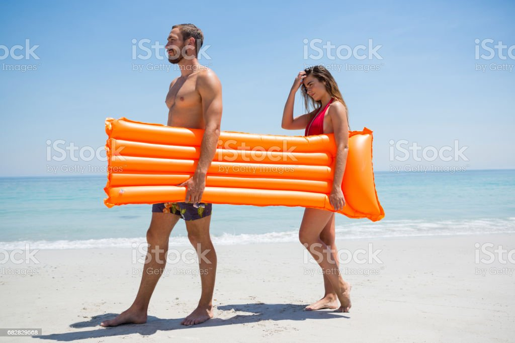 Seitenansicht des Paares tragen Pool Floß Lizenzfreies stock-foto