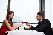 side view of couple clinking glasses of red wine while celebrating st valentine day in restaurant