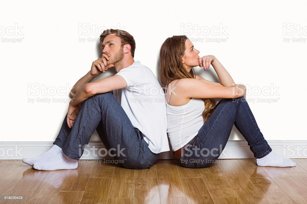 Side view of couple sitting on floor stock photo