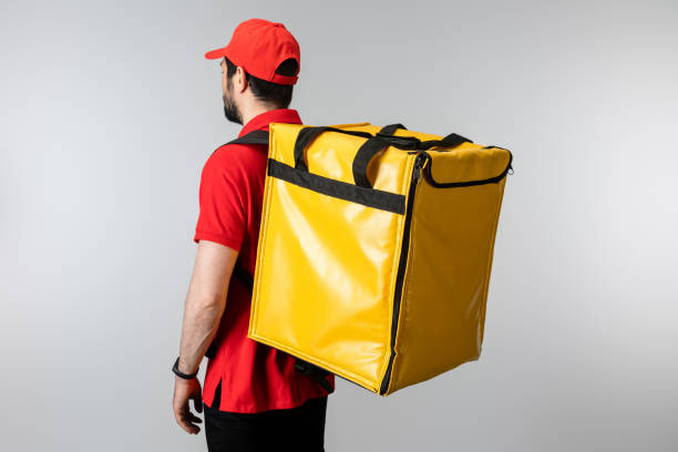 Side view of courier with thermo backpack isolated on grey stock photo