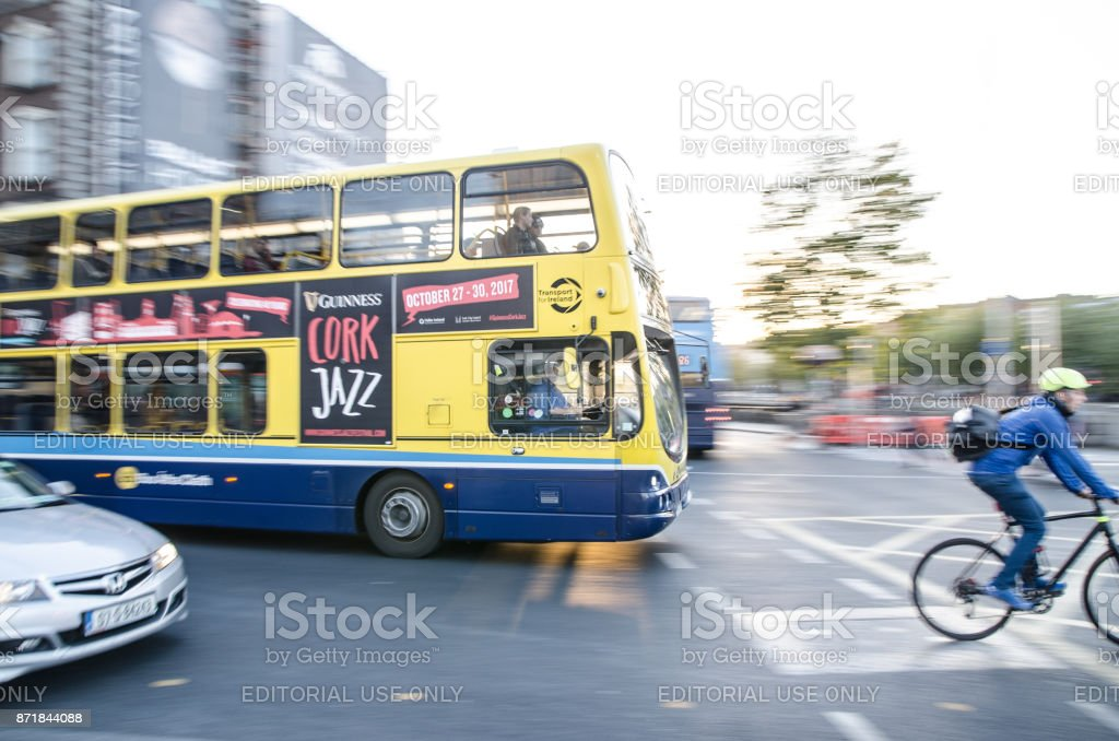 Side view of cyclist in front of a double-decker bus in downtown O'Connell street of Dublin Ireland during rush hour a day of autumn stock photo