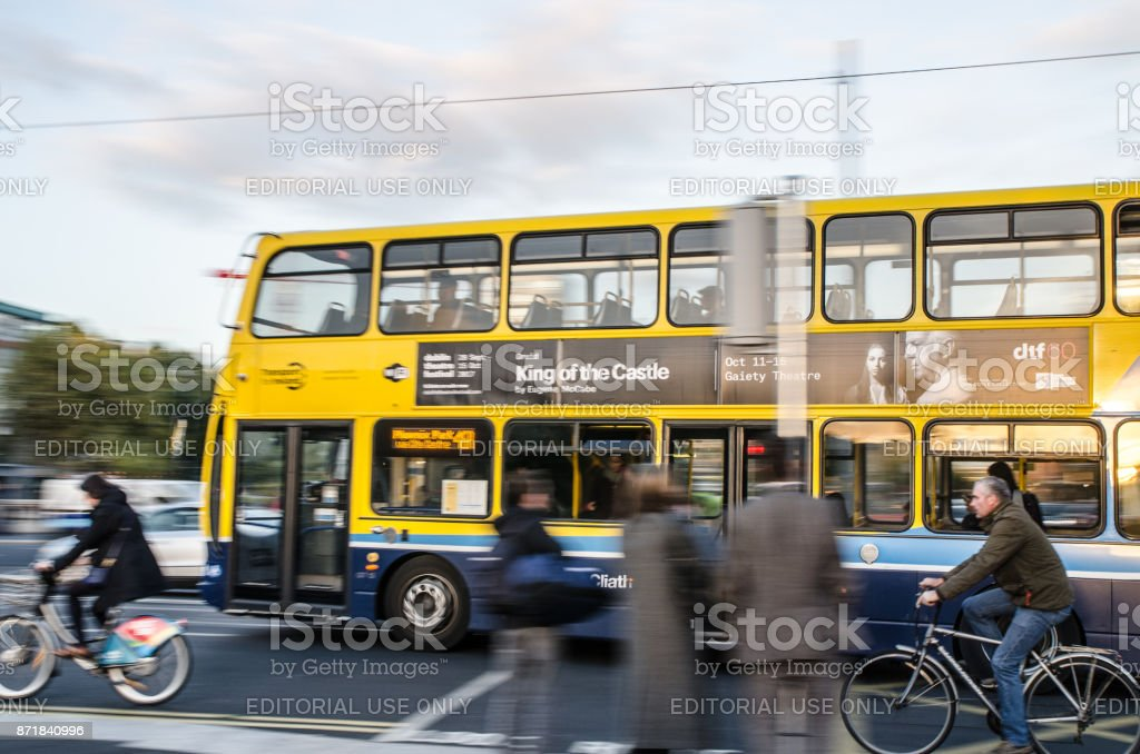 Side view of cyclists besides of a double-decker bus in downtown O'Connell street of Dublin Ireland during rush hour a day of autumn stock photo