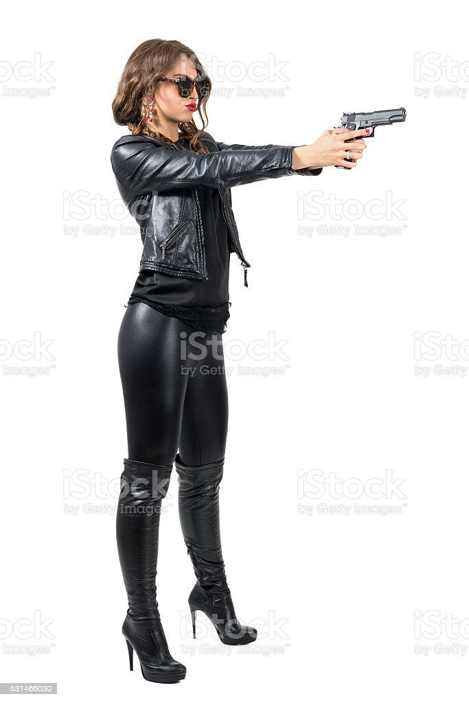 Side view of dangerous woman in leather clothes shooting gun stock photo