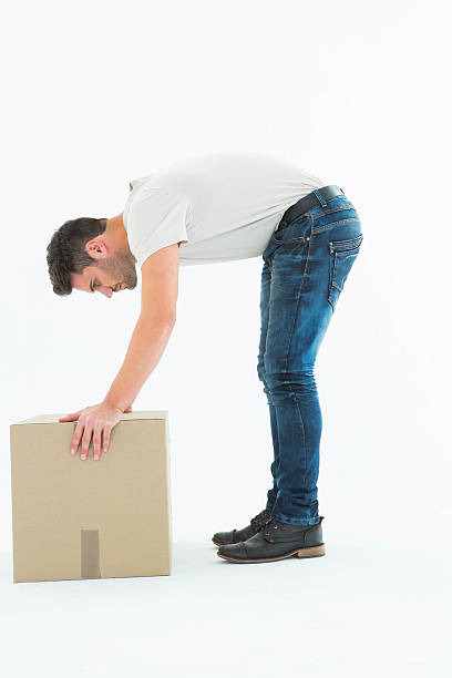 Side view of delivery man picking cardboard box stock photo