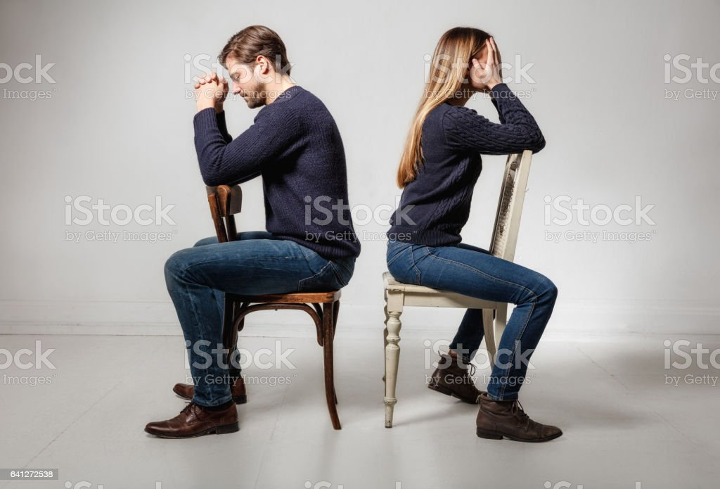 Side view of depressed couple sitting back to back on chairs stock photo