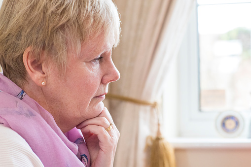 874789168 istock photo Side View Of Depressed Senior Woman At Home 941420794