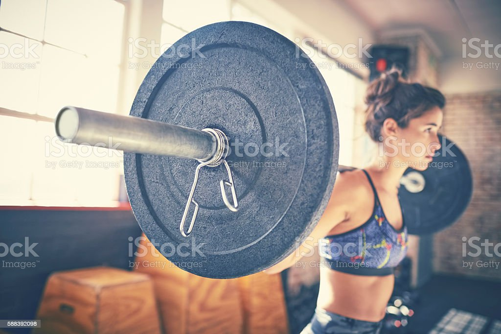 Side view of determined woman picking up barbell in gym stock photo