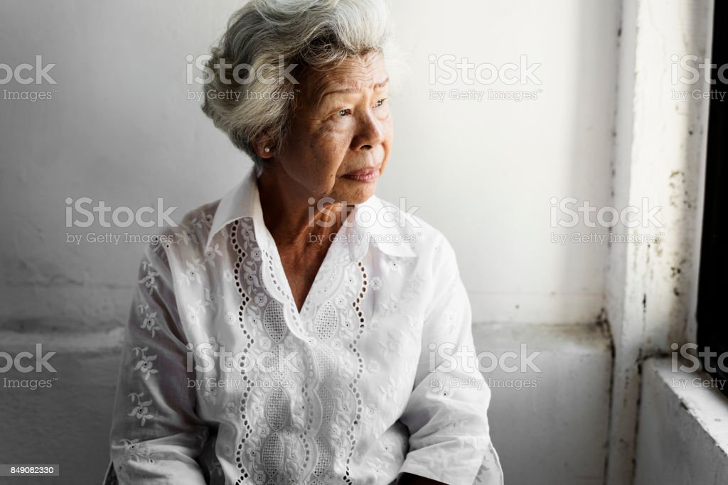 Side view of elderly asian woman with thoughtful face expression stock photo