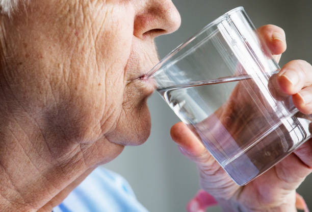 Side view of elderly woman drinking water Side view of elderly woman drinking water eastern european descent stock pictures, royalty-free photos & images