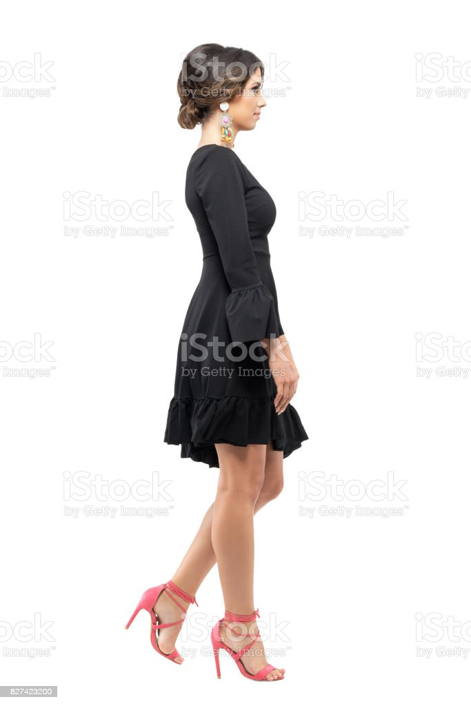 Side view of elegant woman in black dress and high heels walking and looking ahead stock photo