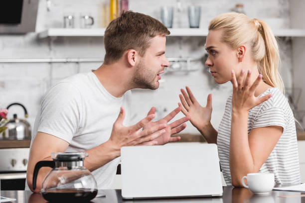 side view of emotional young couple arguing and looking at each other in kitchen, relationship difficulties concept side view of emotional young couple arguing and looking at each other in kitchen, relationship difficulties concept arguing stock pictures, royalty-free photos & images