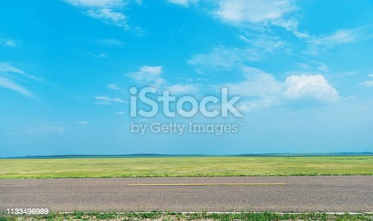 Side view of empty asphalt road and green field.