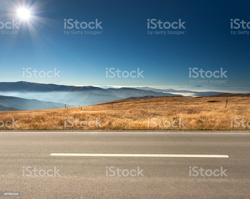 Side view of empty highway in mountain range stock photo