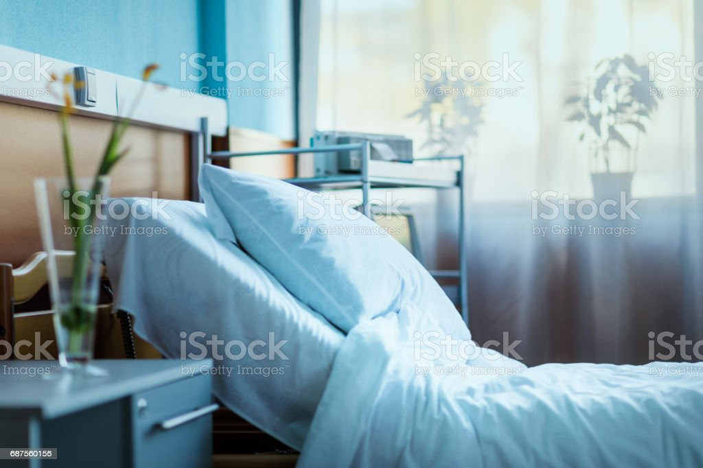 side view of empty hospital bed in clinic chamber stock photo