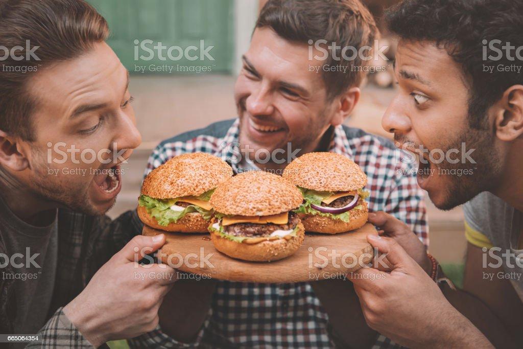 Seitenansicht des begeistert junge Männer frische leckere Hamburger beißen Lizenzfreies stock-foto
